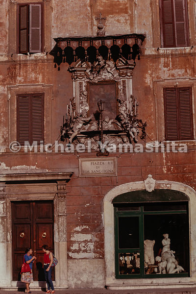 Women converse next to a window with sculptures in the Piazza di Tor Sanguigna. Rome, Italy, 1988.