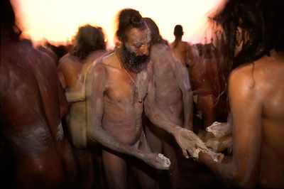 India - Allahabad - Saddhus smear themselves with ash before they bathe at the Kumbh Mela. Ardh Kumbh Mela 1995, Allahbad, India