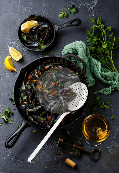 Mussels in black cooking pan with parsley and wine on dark stone background