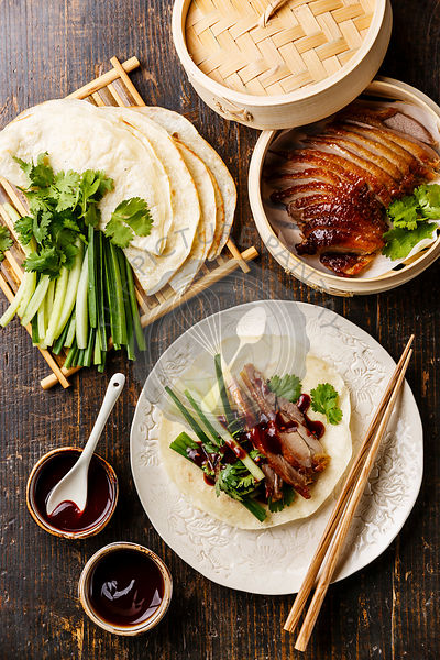 Peking Duck served with fresh cucumber, green onions, cilantro and roasted wheaten chinese pancakes with sauce Hoysin on wooden background