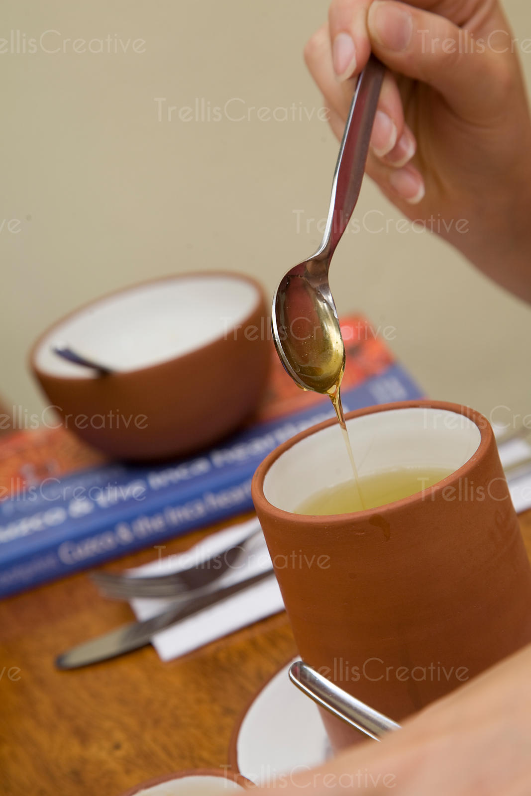 A young woman pours honey into hot herbal tea