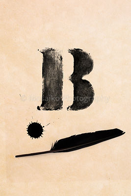 Old black, frayed grunge B - letter, inkblot and black feather on brown paper