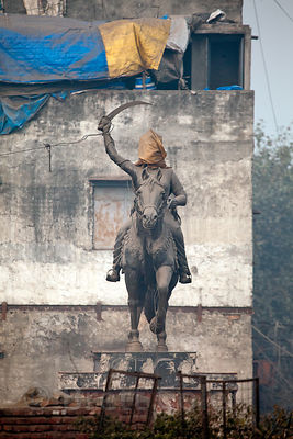 Statue with its head covered in the Khari Baoli area of Old Delhi, India