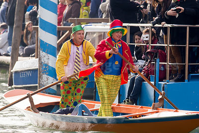 Man & Woman in Bright Colourful Clown Costumes vigorously rowing in the Venice Carnival Water Parade