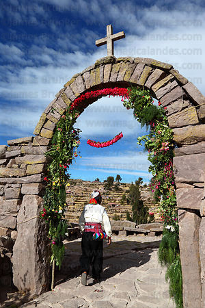 Man passing stone arch decorated with kantuta flowers ( Cantua buxifolia ) for San Santiago festival , Taquile Island , Peru