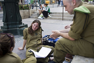 Israel - Jerusalem - Off duty soldiers sit and talk on some steps in Ben Yahuda Street