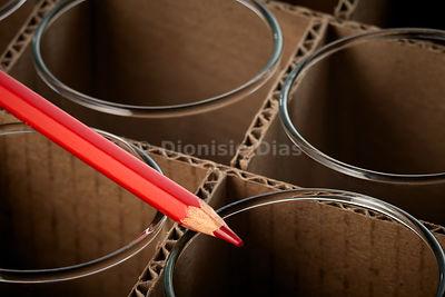Red pencil over crate of corrugated cardboard