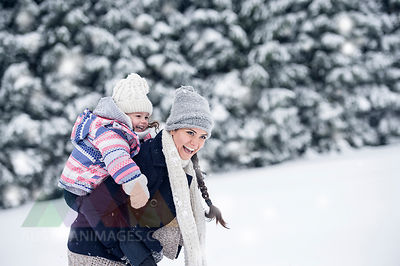 Happy mother carrying daughter piggyback in winter landscape