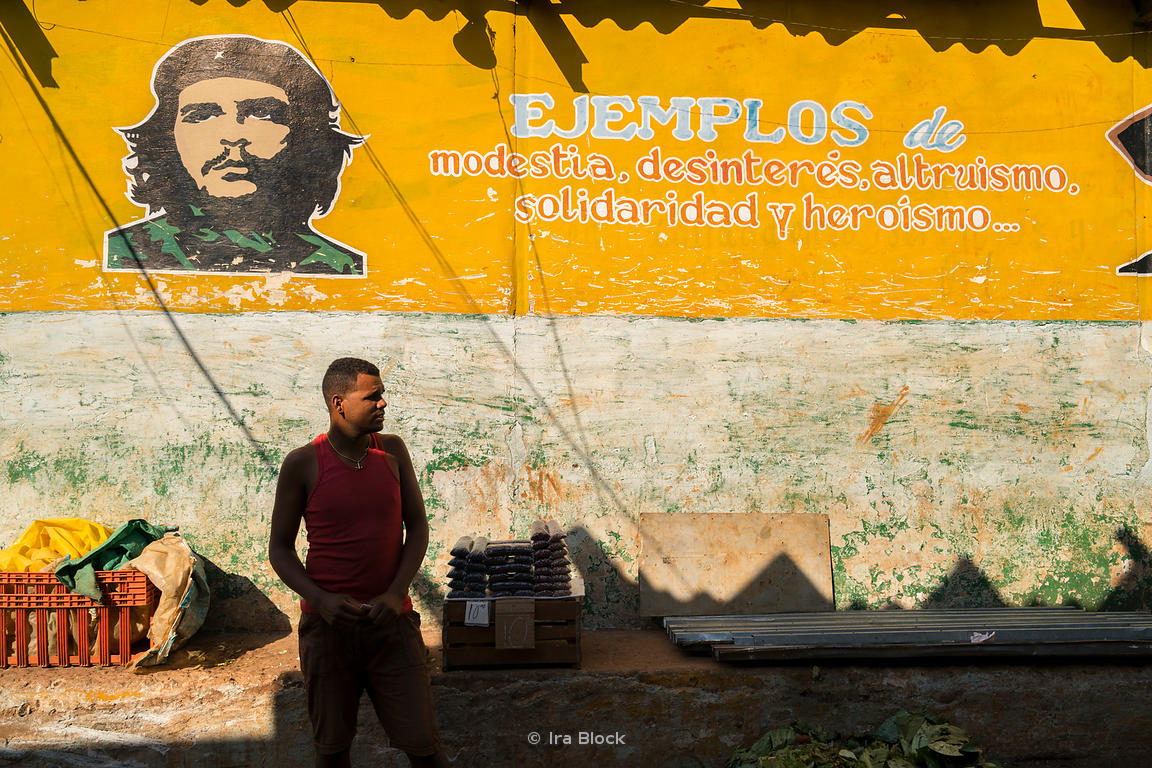A man at a local market in Havana, Cuba with a Che Guevara sign in the background.