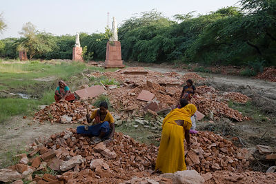 India - Delhi - Women demolish plinths and pavement around statues of King George V and other Imperial notables and Viceroys at the Coronation Durbar site near Delhi, India. The statues were removed from New Delhi in the 1960's. The statue of George V ori
