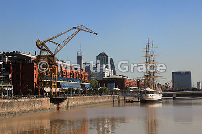 Puerto Madero docklands regeneration in Buenos Aires, Argentina with brick warehouse, crane and Presidente Sarmiento frigate