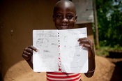 Kenyan child showing spelling work done at school on a sheet of paper.