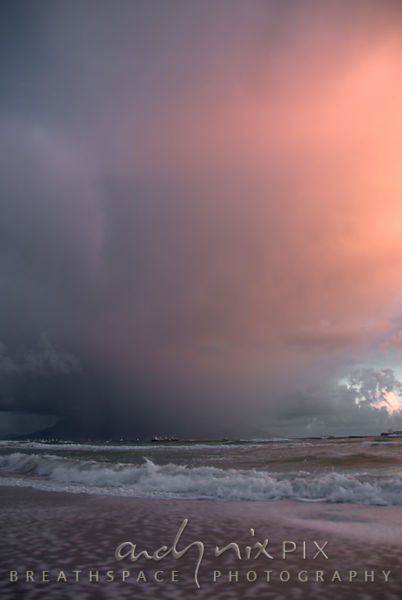 Viewed from Blouberg Beach, a sunset squall passes over Table Bay, obscuring Table Mountain. The setting sun lights up some clouds in pink, contrsating withe the dark storm clouds.