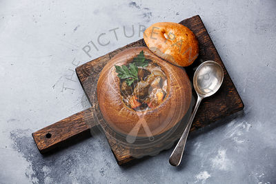 Beef meat soup Goulash stewed with potato, carrot and spices in Bread on concrete background