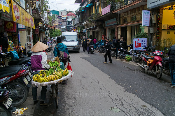 A person walking with bananas on bicycle in the street
