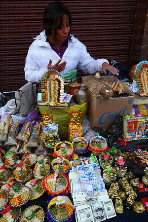 Woman selling pots of seeds , miniature money bundles and other lucky charms in market for Alasitas festival, Puno, Peru