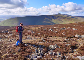 A hiker checking their position on a GPS map near the summit of Carrock Fell with views of Bowscale Fell and Blencathra in the distance in the English Lake District, UK.