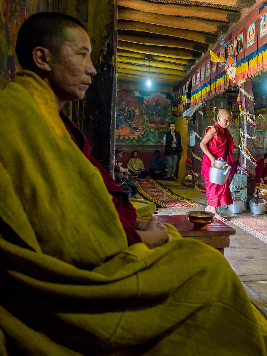 A monk overlooks while a young monk serves tea to the visitors