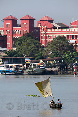 A low-tech sailboat on the Hoogly River, Kolkata, India. In the background is the massive Howrah Railway Station.