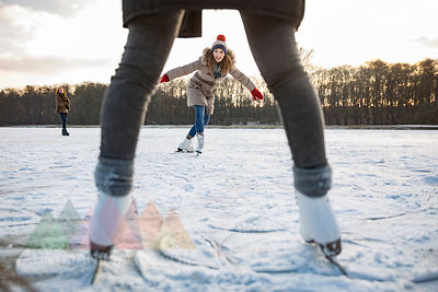 Woman ice skating on frozen lake with friends