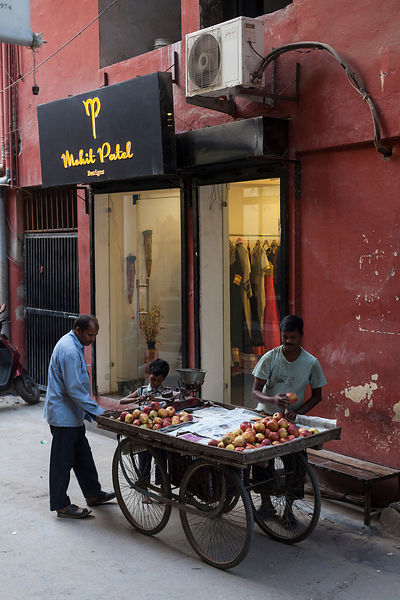 India - Delhi - A fruit vendor outside a modern upscale shop in the trendy village of Sharpur Jat now home to expensive couture and the burgeoning fashion industry