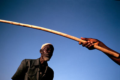A neighbour holds Asiah Anafo?Äôs stick for him to guide his hoe, Arigu, Northern Ghana
