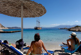 Three masted wooden sailing ship and sun bathers, Kania Beach, Chalki Island near Rhodes, Dodecanese Islands, Greece.