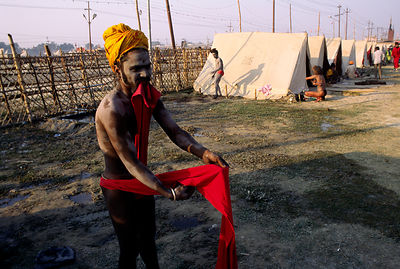 India - Allahbad - A saddhu dresses at his camp
