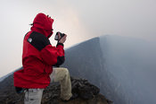 Tourist standing on the rim of Nyiragongo Volcano, Virunga National Park, DR Congo