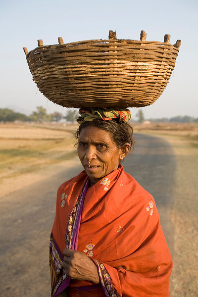 A tribal woman carries nahua flowers in a basket
