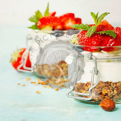 Homemade granola muesli with nuts and dried fruits and yogurt in glasses on rustic wooden background. Healthy breakfast.