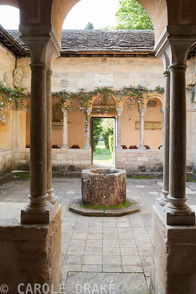 Open court in centre of the Cloisters with well head from a convent in Aquilegia, and Clematis montana trained around the walls. Iford Manor, Bradford-on-Avon, Wiltshire