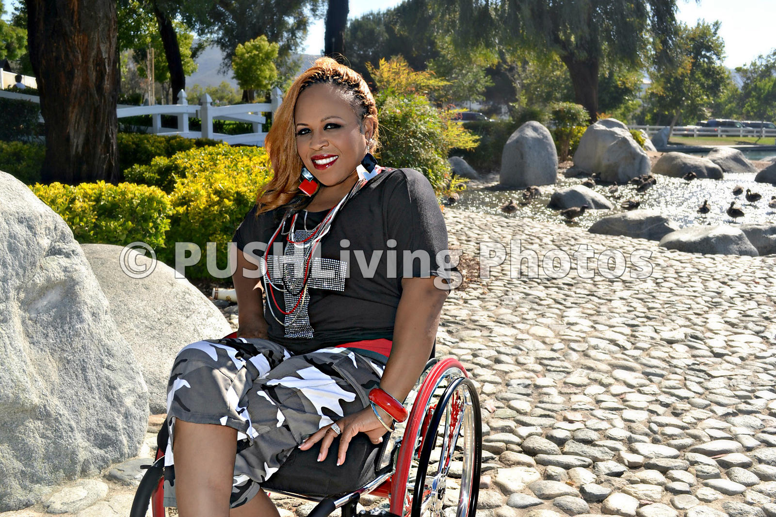 Woman in a wheelchair enjoying a lakeside park