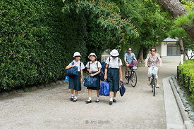Japanese girls in school uniforms and tourists on bicycles in Tokyo, Japan.