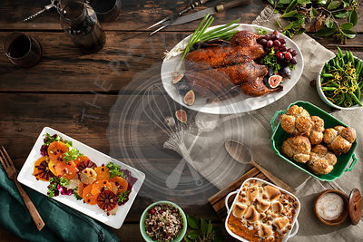 An overhead view of a holiday dinner with roasted duck, citrus salad, rice, green beans, rolls, sweet potato casserole and wine. Warm, moody tones on rustic wood tabletop.