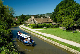 Narrow boat sailing past the George Inn on the Kennet and Avon Canal, Bathampton near Bath, Somerset, England.