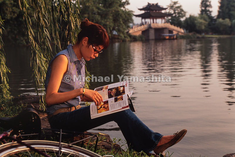 A young lady enjoys the lake and view of Rainbow bridge on West Lake in Hangzhou, China.