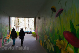 couple walking by a painted wall