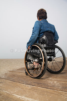 Woman in a wheelchair on a beachside boardwalk