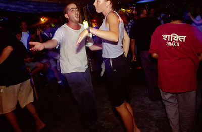 Two young travellers dance at a bar