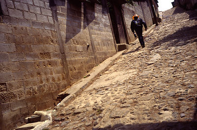 A man walks up a street in a village on the outskirts of Guatemala city