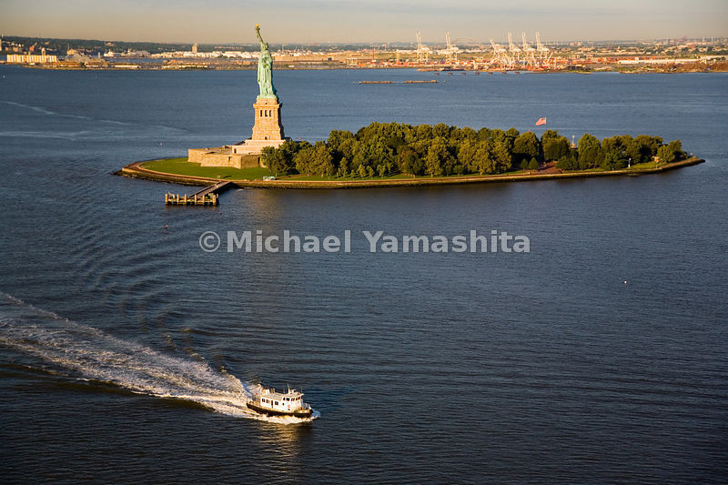 The Lady of Liberty, a gift to the U.S. from the people of France in 1886, holds her torch aloft on her perch on Liberty Island as a tug boat cruises by.