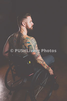 Studio shot of a tatooed man using a wheelchair