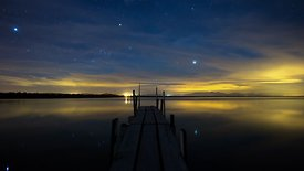 Medium Shot: Galaxies & Planets' Movement Reflecting In The Stillness Of The Salton Sea (Night to Day)
