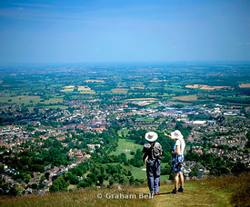 a couple of walkers taking in the view from north hill, malvern hills, great malvern, worcestershire