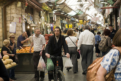 Israel - Jerusalem - An Orthodox Jewish man on a bicycle shopping at the Mahane Yahuda Market