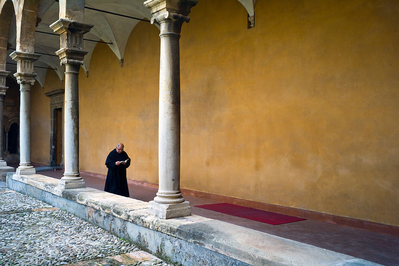 Italy - Palermo - A priest reads as he walks through cloisters in the courtyard of the Saint Augustino Church