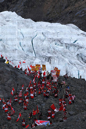 Spiritual leaders descending from glaciers after performing overnight rituals to mountain spirits during Qoyllur Riti festival, Peru