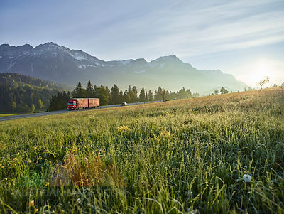 Austria, Tyrol, truck on country road in the morning light