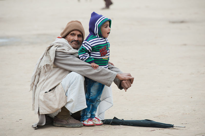 A grandfather holds on to his grandson dearly, during the kumbh mela.